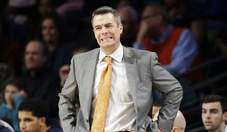 FILE - In this Jan. 9, 2016, file photo, Virginia head coach Tony Bennett watches from the sideline during the first half of an NCAA college basketball game against Georgia Tech, in Atlanta. Virginia coach Tony Bennett responded defiantly before the complete question was even asked about his team's defensive philosophy.  No, he said, No. 13 Virginia has not changed its identity from a defense-minded team to one focuses more on offense. The coach also said if the Cavaliers want to reach their potential, they need to start playing better defense.  (AP Photo/David Goldman, File)