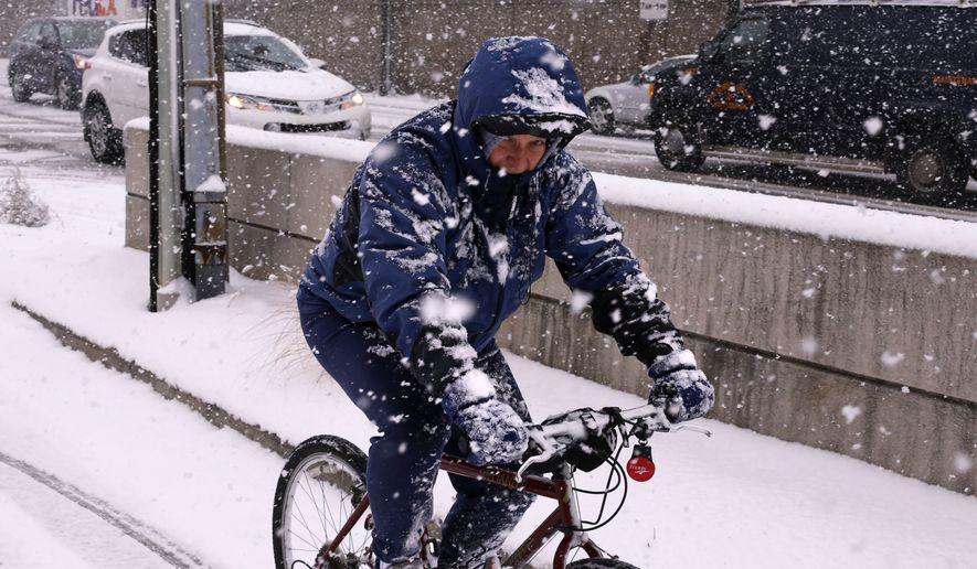 A bicyclist rides through downtown Pittsburgh during a mid-day snow fall, Tuesday, Jan. 12, 2016. (AP Photo/Gene J. Puskar)