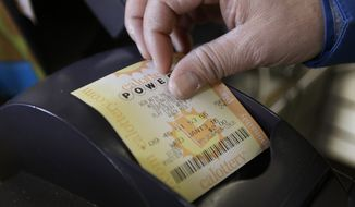 A store clerk removes a Powerball quick pick lottery ticket Wednesday in Oakland, Calif. (Associated Press)