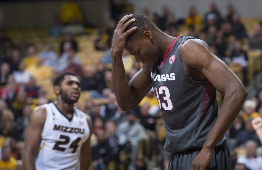 Arkansas' Moses Kingsley, right, holds his head as Missouri's Kevin Puryear walks in the background, after Kingsley was fouled during the second half of an NCAA college basketball game, Tuesday, Jan. 12, 2016, in Columbia, Mo. Arkansas won the game 94-61. (AP Photo/L.G. Patterson)