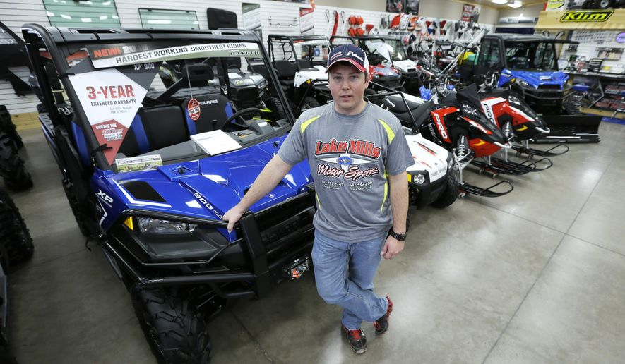 In this Dec.16, 2015 photo, Michael Rygh stands near all-terrain vehicles at his dealership in Algona, Iowa. The buzzy, open-air vehicles are supposed to be banned from roads in New York and other states. But small communities across the nation are increasingly bending the rules under pressure from riders who want to go wherever they please, even though ATV manufacturers warn that the vehicles are unstable on flat pavement and accidents kill more than 300 riders each year. (AP Photo/Charlie Neibergall)