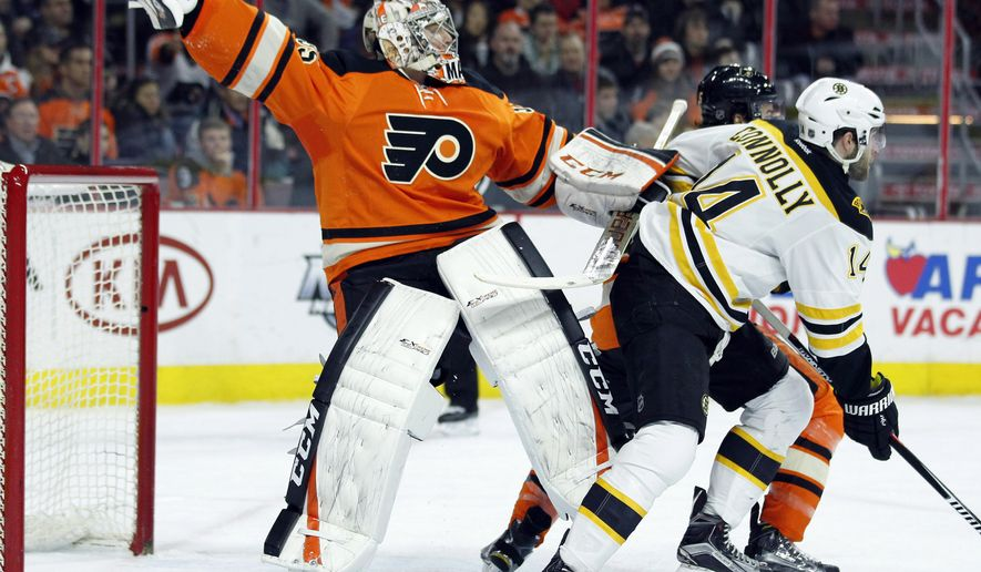 Philadelphia Flyers' Steve Mason, left, falls after colliding with Boston Bruins' Bret Connolly, right, during the first period of an NHL hockey game Wednesday, Jan 13, 2016, in Philadelphia.  (AP Photo/Tom Mihalek)