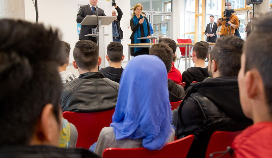 In this picture taken Monday, Jan. 11, 2016, Bavarian Minister for Justice Winfried Bausback talks to migrants at a school in the Bavarian town of Ansbach, southern Germany. Some 800 German judges, prosecutors and judicial officers are beginning to teach newly arrived asylum seekers the basics of law in their new host country. The legal primer classes for refugees in the southern state of Bavaria include lessons about freedom of opinion, the separation of religion and state and the equality of men and women. (Daniel Karmann/dpa via AP)