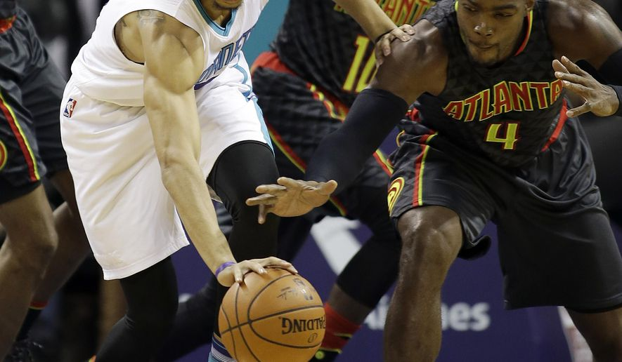 Charlotte Hornets' Jeremy Lamb, left, controls a loose ball away from Atlanta Hawks' Paul Millsap, right, during the first half of an NBA basketball game in Charlotte, N.C., Wednesday, Jan. 13, 2016. (AP Photo/Bob Leverone)