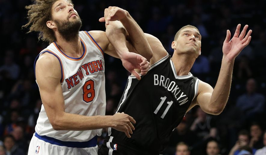 New York Knicks' Robin Lopez (8) and Brooklyn Nets' Brook Lopez (11) fight for position during the first half of an NBA basketball game Wednesday, Jan. 13, 2016, in New York. (AP Photo/Frank Franklin II)