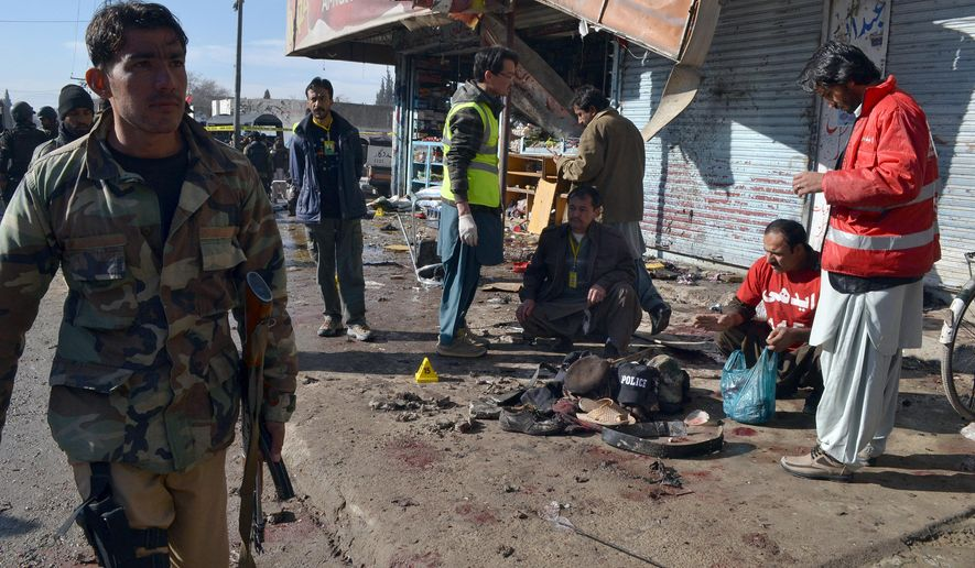 Pakistani police officer and rescue workers gather at the site of suicide bombing in Quetta, Pakistan, Wednesday, Jan. 13, 2016. The suicide attack on a polio vaccination center in southwestern Pakistan killed more than a dozen people and wounded many, officials said. (AP Photo/Arshad Butt)