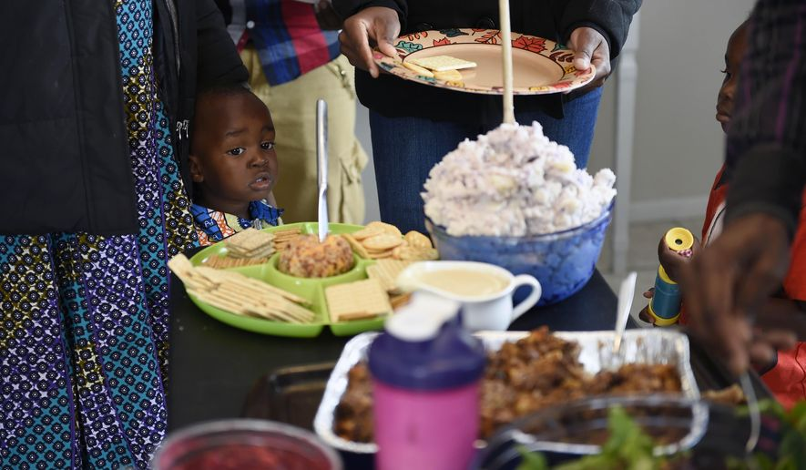 ADVANCE FOR WEEKEND EDITIONS JAN. 16-17 - In this Nov. 26, 2015 photo, Daniel Mulabwe looks at all the food during Thanksgiving Day dinner at the Bangerter's home in Twin Falls, Idaho. After three years of awaiting approval, Kanegamba Mulabwe, 26, Bahati, 22, and their children, Sarah, 3, and Daniel, 1, passed security checks and were approved to come to the U.S. (Drew Nash/The Times-News via AP) MANDATORY CREDIT