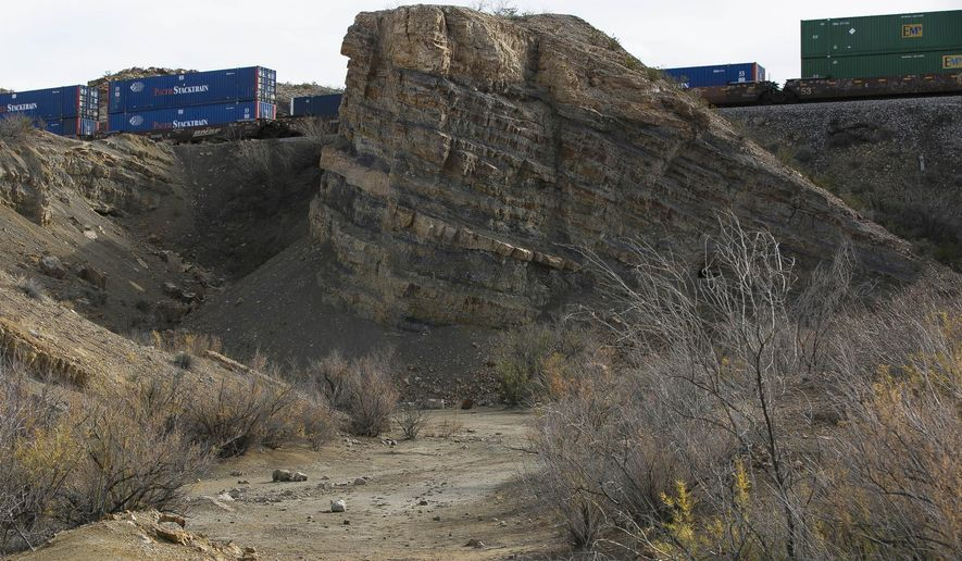 In this Jan. 7, 2016 photo, a train passes by behind Track 1 of the Insights Science Center New Mexico Dinosaur Trackways, off Brickland Road in Sunland Park, N.M., which is located near the starting area of the proposed Rio Grande Trail. (Robin Zielinski/The Las Cruces Sun-News via AP) MANDATORY CREDIT