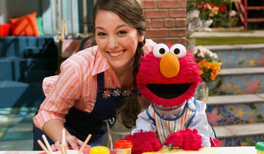 """This image released by the Sesame Workshop, Suki Lopez, as Nina, left, and character Elmo appear on """"Sesame Street."""" The popular children's show begins its 46th season on HBO on Saturday, Jan. 16, 2016. (Richard Termine/Sesame Workshop via AP)"""