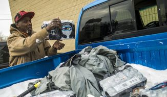 Flint resident Herbert Biggs, 59, throws a case of bottled water in the back of his truck, as he gathers water for his neighborhood on Wednesday, Jan. 13, 2016, at a fire station in Flint, Mich. The first seven Michigan National Guard soldiers are on the ground at fire stations throughout the city, assigned by Gov. Rick Snyder on Tuesday to help distribute water and relieve residents in relation to the Flint water crisis. (Jake May/The Flint Journal-MLive.com via AP)