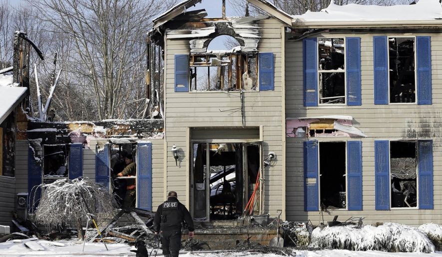 Investigators search a deadly house explosion, Tuesday, Jan. 12, 2016, in Northfield Center Township, Ohio. The blast and subsequent fire happened Monday night. (AP Photo/Tony Dejak)