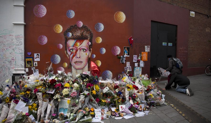 A man kneels down to lift a women up on his shoulders as they try to put up a picture beside tributes around a mural of British singer David Bowie by artist Jimmy C in Brixton, south London, Thursday, Jan. 14, 2016. Bowie, the other-worldly musician who broke pop and rock boundaries with his creative musicianship, nonconformity, striking visuals and a genre-spanning persona he christened Ziggy Stardust, died of cancer Sunday aged 69. He was born in Brixton. (AP Photo/Matt Dunham)