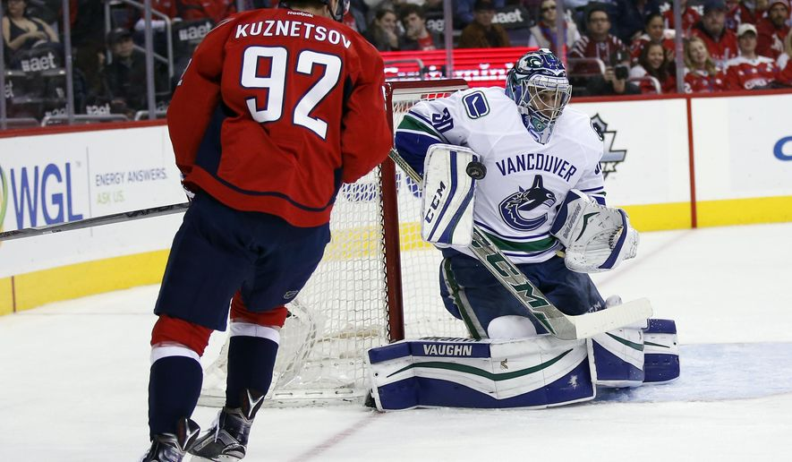 Vancouver Canucks goalie Ryan Miller (30) blocks a shot as Washington Capitals center Evgeny Kuznetsov (92), from Russia, waits for the rebound, in the first period of an NHL hockey game, Thursday, Jan. 14, 2016, in Washington. (AP Photo/Alex Brandon)