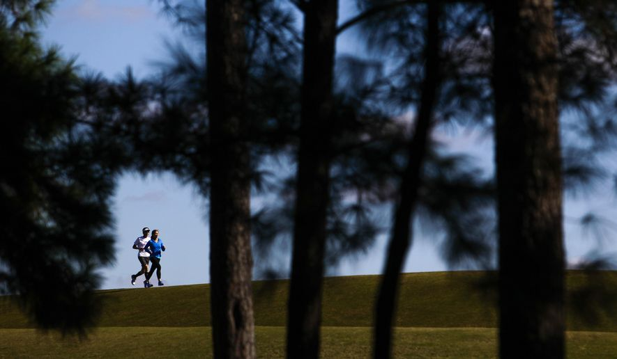 In this photo taken Saturday, Jan. 9, 2016, Lindsay McClelland, right, and her father, Alan McClelland, pose for a portrait at Hermann Park in Houston. The two have been training together and will be running in Sunday's Houston Marathon. ( Michael Ciaglo/Houston Chronicle via AP) MANDATORY CREDIT