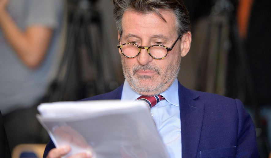 IAAF-President Sebastian  Coe takes a look at a paper during a  press conference about WADA's Independent Commission Report in Munich, Germany, on Thursday, Jan. 14, 2016. (AP Photo/Kerstin Joensson)