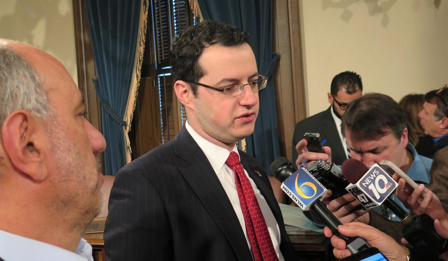 State budget director John Roberts speaks with reporters after a biannual revenue-estimating meeting on Thursday, Jan. 14, 2016, in the Capitol in Lansing, Mich. He said Michigan has a one-time budget surplus of $575 million, some of which will be used to address lower tax revenue estimates for the current budget and to bolster savings.[AP Photo/David Eggert]