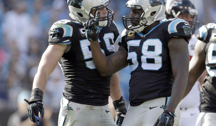 FILE - In this Dec. 13, 2015, file photo, Carolina Panthers' Thomas Davis (58) celebrates after a play against the Atlanta Falcons with Luke Kuechly (59) in the first half of an NFL football game in Charlotte, N.C. Panthers All-Pro linebackers Luke Kuechly and Thomas Davis continue to push each other to new heights. Carolina will host Seattle on Sunday in an NFC divisional playoff game.(AP Photo/Bob Leverone, File)
