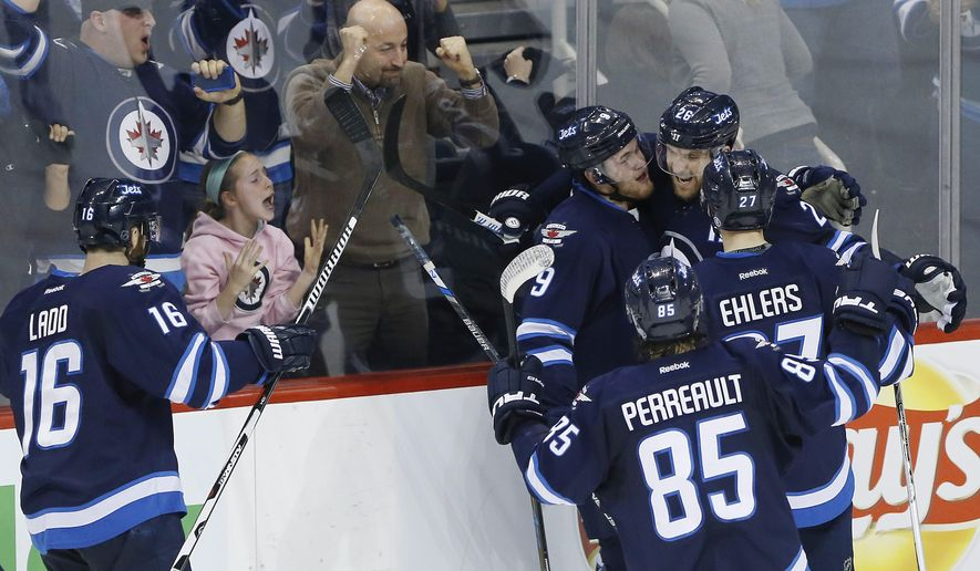 Winnipeg Jets' Andrew Ladd (16), Andrew Copp (9), Mathieu Perreault (85), Blake Wheeler (26) and Nikolaj Ehlers (27) celebrate Wheeler's goal during overtime against the Nashville Predators on Thursday, Jan. 14, 2016, in Winnipeg, Manitoba. (John Woods/The Canadian Press via AP)