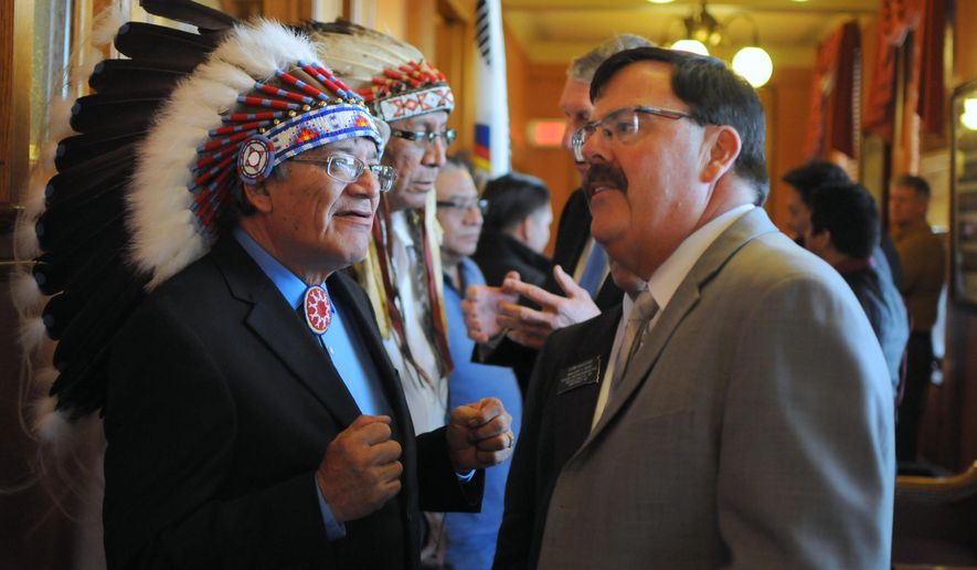 """Oglala Sioux tribal President John Yellow Bird Steele, left, speaks with Lt. Gov. Matt Michels before the State of the Tribes address on Thursday, Jan. 14, 2016, at the state Capitol in Pierre, S.D. Yellow Bird Steele called Medicaid expansion a """"win-win"""" for the state and South Dakota Native American tribes. (AP Photo/James Nord)"""