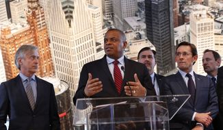 U.S. Transportation Secretary Anthony Foxx, second from left, speaks as auto executives listen at the North American International Auto Show in Detroit, Thursday, Jan. 14, 2016. Foxx said Thursday that the National Highway Traffic Safety Administration also will develop a model policy for states to follow if they decide to allow autonomous cars on public roads. That policy — which will be developed within six months — could help form the basis of a consistent national policy. (AP Photo/Paul Sancya)