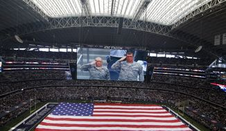 American service man salute as a large flag is unfurled over the field at AT&T Stadium during the playing of the national anthem before an NFL football game against the Washington Redskins on Sunday, Jan. 3, 2016, in Arlington, Texas. (AP Photo/Roger Steinman)