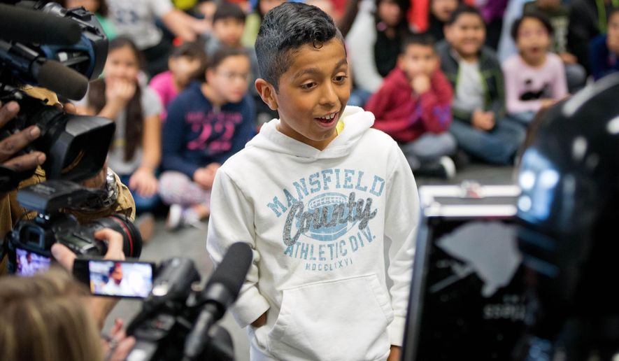 In this Thursday, Jan. 14, 2016, photo, Alvin Garcia Flores reacts to seeing his bionic arm for the first time in Omaha, Neb. Garcia Flores, a 4th-grade student at Gateway Elementary School in Omaha, received a 3D-printed bionic arm from Limbitless Solutions, which was delivered by volunteers from the 501st Legion, the national fan organization for Star Wars. (Matt Miller/The World-Herald via AP) MAGS OUT; ALL NEBRASKA LOCAL BROADCAST TELEVISION OUT; MANDATORY CREDIT