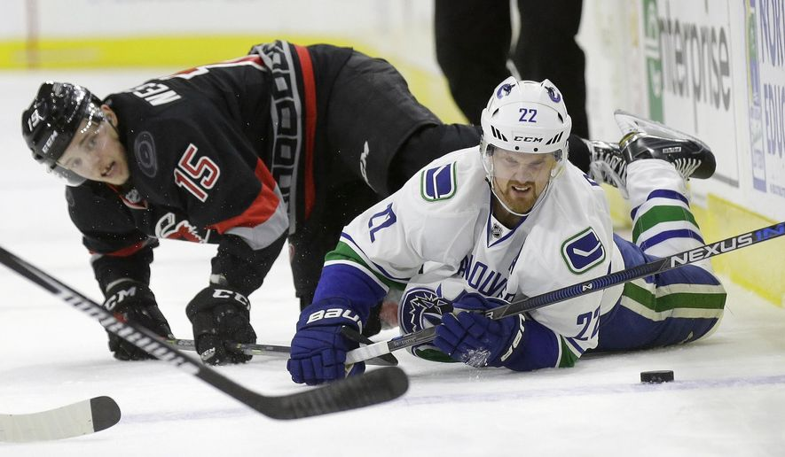 Carolina Hurricanes' Andrej Nestrasil (15), of the Czech Republic, and Vancouver Canucks' Daniel Sedin (22), of Sweden, fall to the ice while chasing the puck during the second period of an NHL hockey game in Raleigh, N.C., Friday, Jan. 15, 2016. (AP Photo/Gerry Broome)