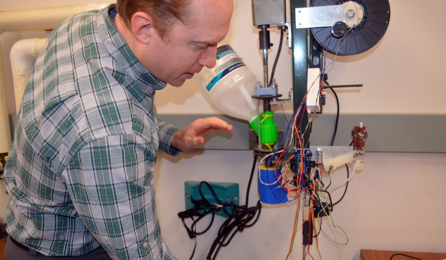 ADVANCE FOR MONDAY, JAN. 18 AND THEREAFTER- In a photo from Jan. 6, 2016, Michigan Technological University associate professor Joshua Pearce explains the operation of the prototype 3-D printer filament maker his students are making in Houghton, Mich. His students are developing a device called a recyclebot, which will use shredded or pelletized waste plastic to make the printer filament. (Kurt Haughlie/The Daily Mining Gazette via AP) MANDATORY CREDIT