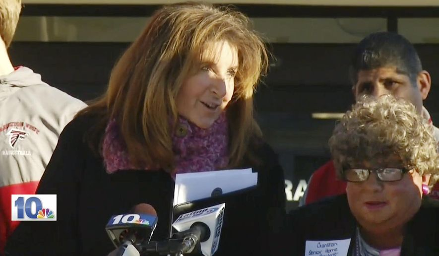 "In this Jan. 5, 2016 still image from WJAR-TV video, Sue Stenhouse, left, executive director of the Senior Enrichment Center, speaks alongside a man dressed as an elderly woman, right, during a news conference in Cranston, R.I., to promote a program for school children to help senior citizens shovel snow during the winter. The middle-aged male bus driver wore a wig, earrings, lipstick and a dress, and a tag that read, ""Cranston Senior Home Resident."" Stenhouse resigned her position after the incident. (WJAR-TV via AP) MANDATORY CREDIT"