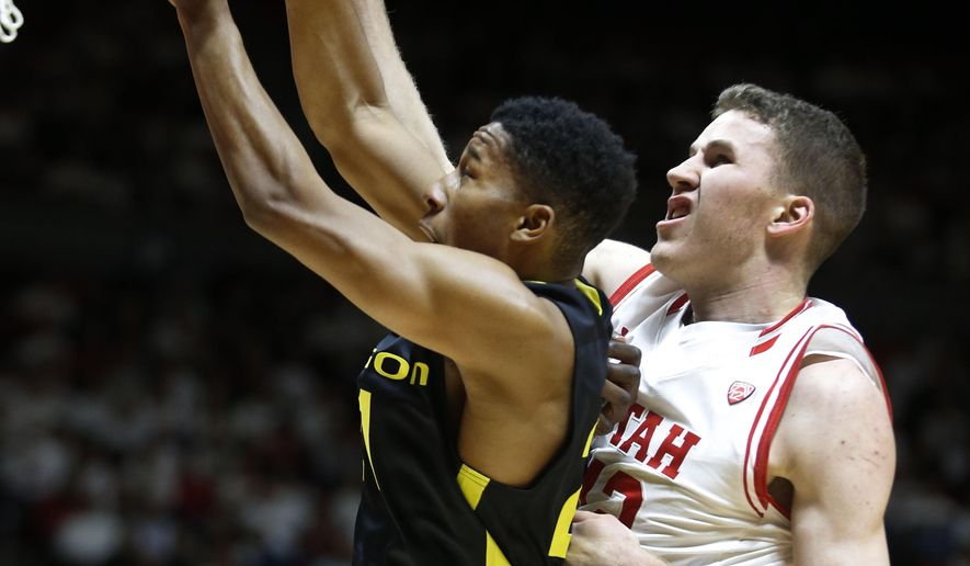 Utah forward Jakob Poeltl, right, and Oregon guard Kendall Small, left, fight for a rebound during the first half of an NCAA college basketball game in Salt Lake City, Thursday, Jan. 14, 2016. (AP Photo/George Frey)