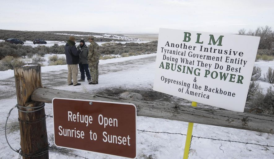 FILE - In this Monday, Jan. 4, 2016 file photo, Members of the group occupying  the Malheur National Wildlife Refuge headquarters stand guard near Burns, Ore. Thousands of archeological artifacts and maps detailing where more can be found are stored at a national wildlife refuge currently being held by a group of armed protestors. (AP Photo/Rick Bowmer, File)