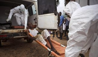 In this file photo taken on Wednesday, Sept. 24, 2014, health care workers load a man suspected of suffering from the Ebola virus onto an ambulance in Kenema, Sierra Leone. A corpse has tested positive for Ebola in Sierra Leone, an official said Friday, Jan. 15, 2016, the day after the World Health Organization declared the outbreak over in West Africa. (AP Photo/ Tanya Bindra,File)