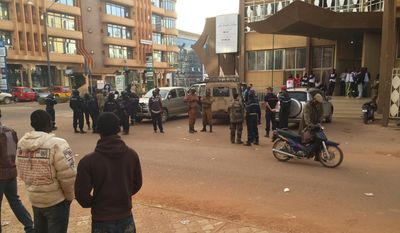 Security forces gather near the Hotel that was attacked by suspected militants in Ouagadougou, Burkina Faso, Saturday, Jan. 16, 2016. Burkina Faso and French forces rescued more people from a luxury hotel in Burkina Faso's capital as they worked to take back the blackened building early Saturday, exchanging heavy gunfire with al Qaeda militants who had seized it the night before. (AP Photo/Ludivine Laniepce )