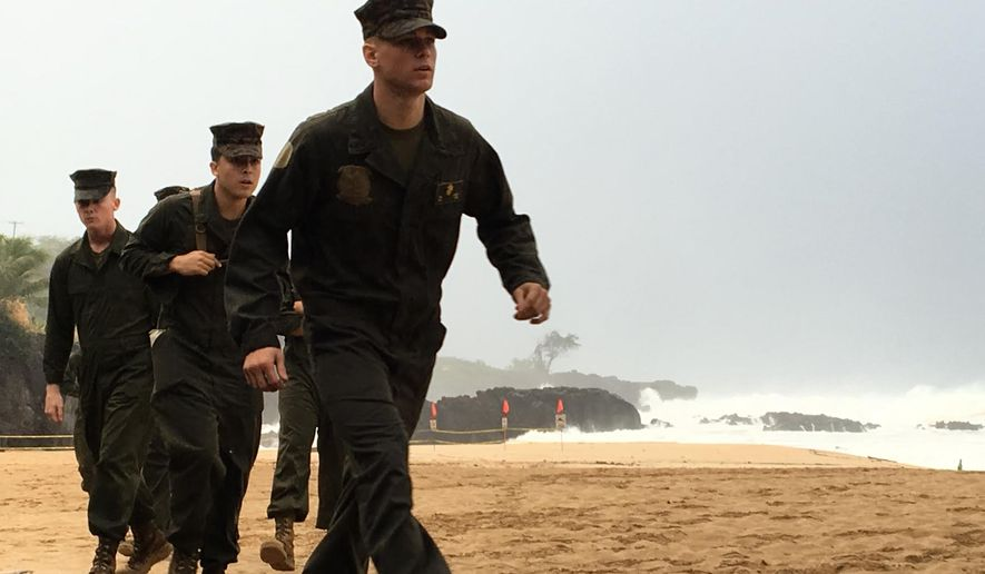 U.S. Marines walk on the beach at Waimea Bay near Haleiwa, Hawaii, where two military helicopters crashed into the ocean about 2 miles offshore, Friday, Jan. 15, 2016. The helicopters carrying 12 crew members collided off the Hawaiian island of Oahu during a nighttime training mission, and rescuers are searching a debris field in choppy waters Friday, military officials said. (Mariana Keller via AP Photo)