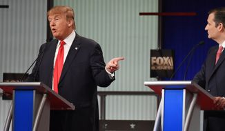 Republican presidential candidate, businessman Donald Trump, left, speaks as Republican presidential candidate, Sen. Ted Cruz, R-Texas, looks on during the Fox Business Network Republican presidential debate at the North Charleston Coliseum, Thursday, Jan. 14, 2016, in North Charleston, S.C. (AP Photo/Rainier Ehrhardt)