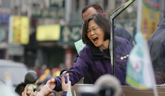 Taiwan's opposition Democratic Progressive Party, DPP, presidential candidate Tsai Ing-wen greets supporters from the back of a truck as she parades through the streets of New Taipei City, Taiwan, Friday, Jan. 15, 2016. (AP Photo/Wally Santana)