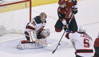 Arizona Coyotes' Shane Doan (19) tries to re-direct the puck past New Jersey Devils goalie Cory Schneider (35) as the Devil's Adam Larsson (5), of Sweden, defends during the second period of an NHL hockey game, Saturday, Jan. 16, 2016, in Glendale, Ariz. (AP Photo/Ralph Freso)