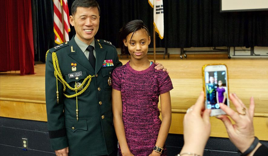 ADVANCE FOR THE WEEKEND OF JAN. 16 - In this Wednesday, Jan. 13, 2016 photo, Maj. Gen. Kyoung Soo Shin, defense attache for South Korea, poses with Caroline Middle School sixth grader Megyn McCoy, 11, at the school in Milford, Va. He discussed the shared history between the two countries and the unity that the school now shares with Korea. (Dave Ellis/The Free Lance-Star via AP) MANDATORY CREDIT