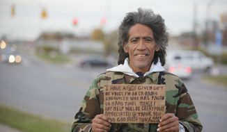 In this December 2010 file photo, Ted Williams holds a sign advertising his smooth radio voice near a highway ramp in Columbus, Ohio. (AP Photo/Columbus Dispatch, Doral Chenoweth III, File)