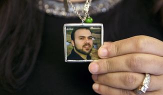 In this June 2, 2015 file photo, Naghmeh Abedini holds a necklace with a photograph of her husband, Saeed Abedini, on Capitol Hill in Washington. Iran state television has reported that the government has released several dual-national prisoners. The Associated Press has confirmed that three of them were Washington Post reporter Jason Rezaian, former U.S. Marine Amir Hekmati and pastor Saeed Abedini. (AP Photo/Jacquelyn Martin, File)