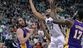 Utah Jazz center Rudy Gobert (27) loses control of the ball while being guard by Los Angeles Lakers defenders Ryan Kelly, left, and Roy Hibbert (17) during the first half of an NBA basketball game Saturday, Jan. 16, 2016, in Salt Lake City.  (AP Photo/Steve Wilson)