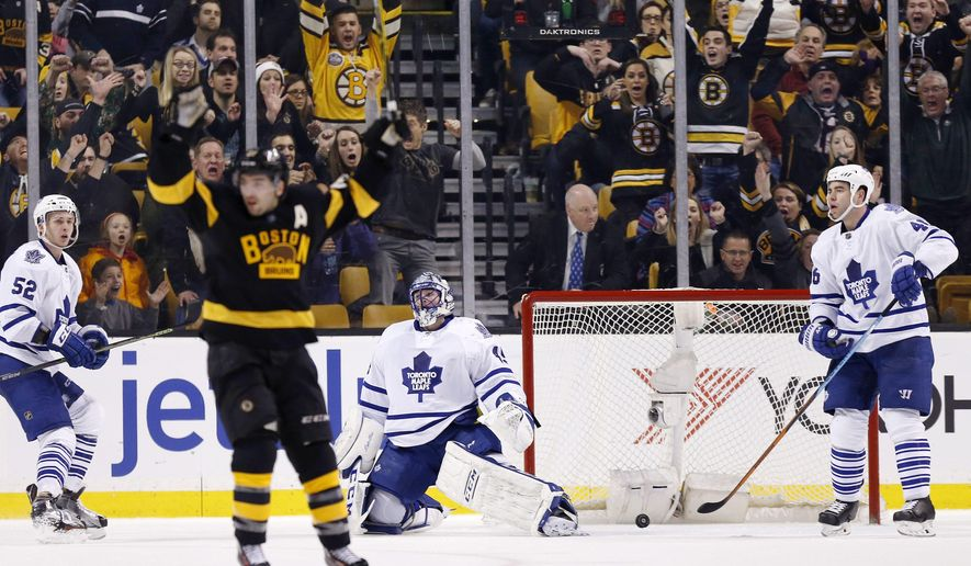 Toronto Maple Leafs' Jonathan Bernier (45) kneels beside the net as Boston Bruins' Patrice Bergeron, foreground, celebrates a goal by Brad Marchand during the third period of an NHL hockey game in Boston, Saturday, Jan. 16, 2016. The Bruins won 3-2. (AP Photo/Michael Dwyer)