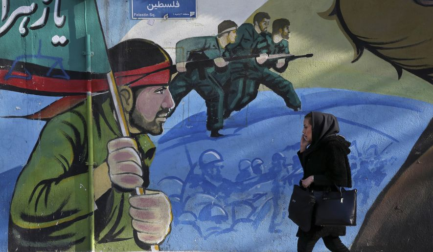 An Iranian woman walks past a mural depicting Iranian armed forces in the battlefield, at Palestine Sq. in Tehran on Jan. 16, 2016. (Associated Press) **FILE**