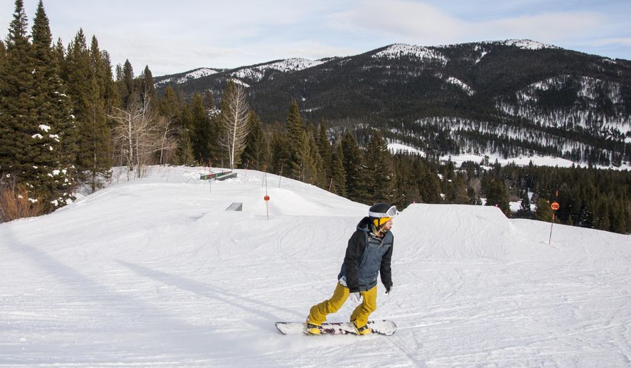 ADVANCE FOR WEEKEND EDITIONS, JAN. 16-17 - In this photo taken Sunday, Jan. 3, 2016, Allison Goebel snowboards off a terrain feature at Bridger Bowl ski area, north of Bozeman, Mont. For a first time snowboarder, it is challenging to start learning without previous experience on skateboarding or surfing. (Marit Ehmke/Bozeman Daily Chronicle via AP) MANDATORY CREDIT