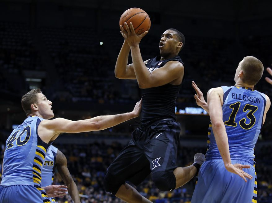 Xavier's Trevon Bluiett is fouled as he shoots against Marquette's Luke Fischer (40) and Henry Ellenson (13) during the second half of an NCAA college basketball game Saturday, Jan. 16, 2016, in Milwaukee. (AP Photo/Morry Gash)