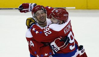 Washington Capitals right wing Justin Williams (14) celebrates his second goal in the third period of an NHL hockey game with center Evgeny Kuznetsov (92), form Russia, Sunday, Jan. 17, 2016, in Washington. Williams scored the empty net goal for a hat trick. The Capitals won 5-2. (AP Photo/Alex Brandon)