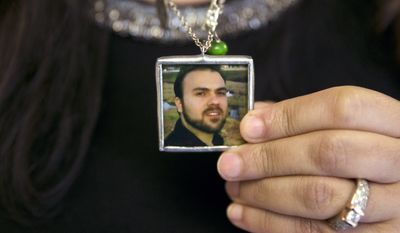 In this June 2, 2015 photo, Naghmeh Abedini holds a necklace with a photograph of her husband, Saeed Abedini, on Capitol Hill in Washington. Iran state television has reported that the government has released several dual-national prisoners. The Associated Press has confirmed that three of them were Washington Post reporter Jason Rezaian, former U.S. Marine Amir Hekmati and pastor Saeed Abedini. (AP Photo/Jacquelyn Martin, File)
