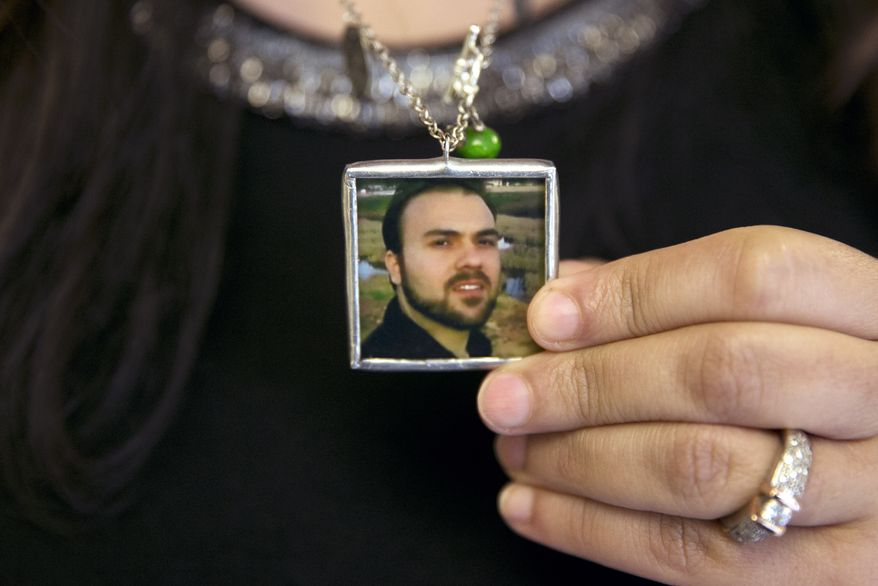 Naghmeh Abedini holds a necklace with a photograph of her husband, Saeed Abedini, on Capitol Hill on June 2, 2015 during a House Foreign Affairs Committee hearing with four people whose family members were being held in Iran. (Associated Press)