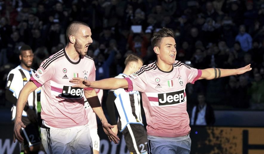 Juventus' Paulo Dybala, right, celebrates after scoring on a penalty kick during the Serie A soccer match between Udinese and Juventus at the Friuli Stadium in Udine, Italy, Sunday, Jan. 17, 2016. (AP Photo/Paolo Giovannini)