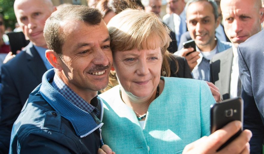 German Chancellor Angela Merkel has pictures taken with refugees in Berlin. (Associated Press/File)
